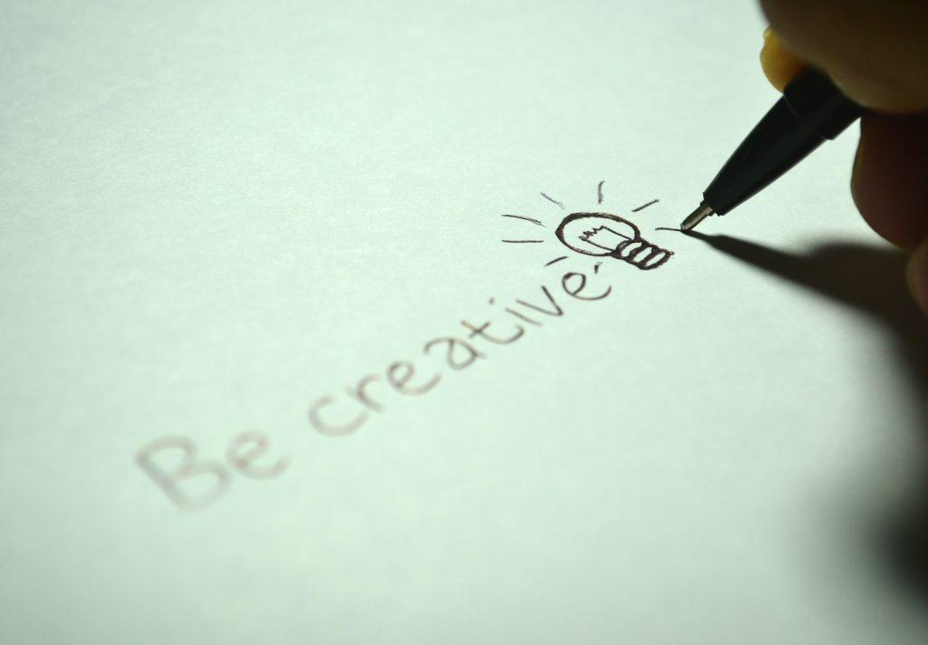 Na foto um papel escrito Be creative com a ponta de uma caneta e uma mão ao final da palavra