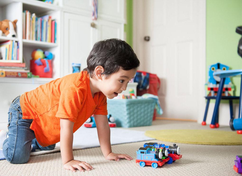 Na foto um menino brincando com um trenzinho de brinquedo.