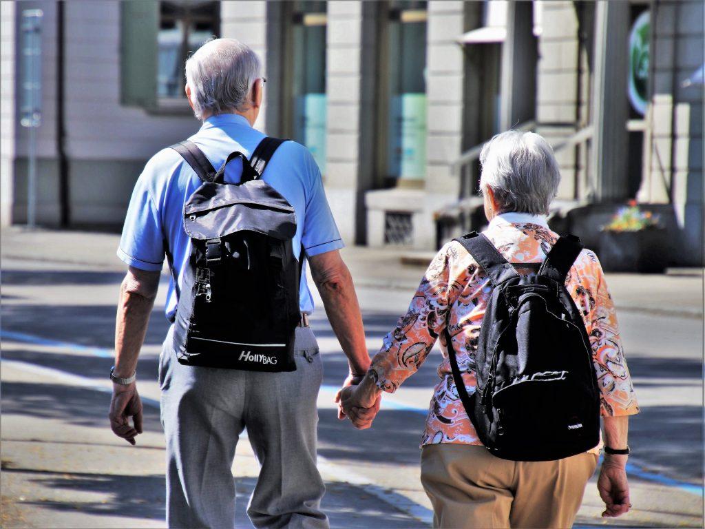 Casal de idosos caminhando de mãos dadas.