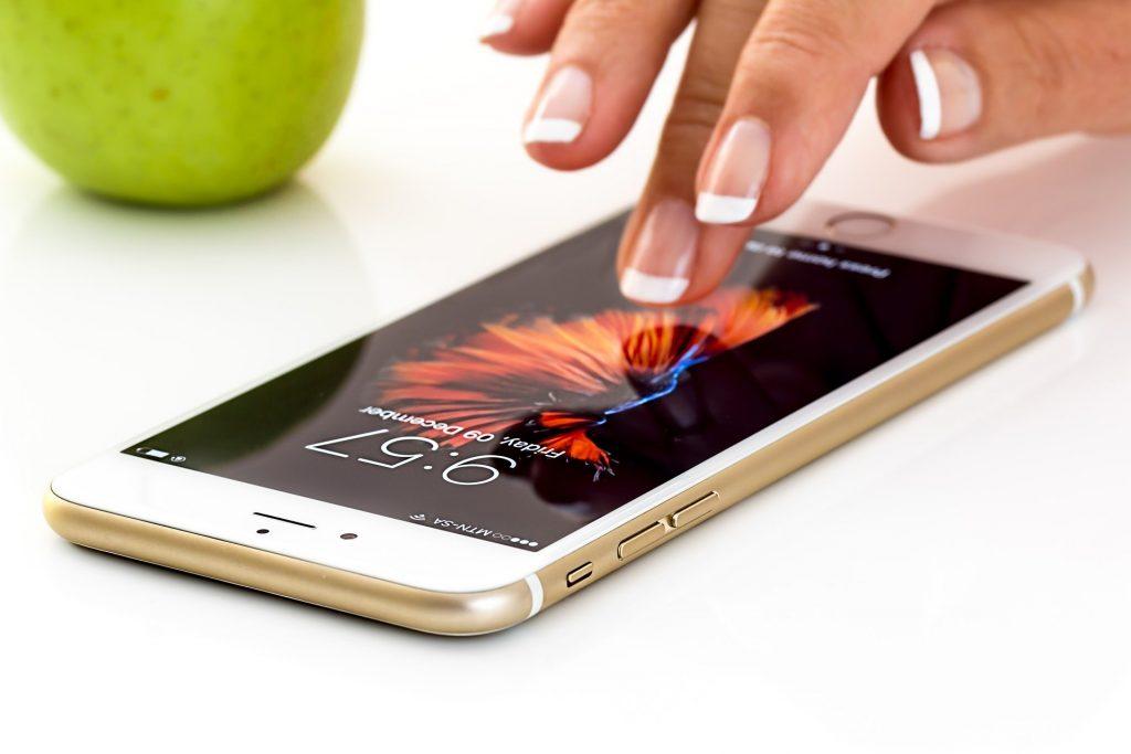 Mão de mulher mexendo em um smartphone sobre a mesa.