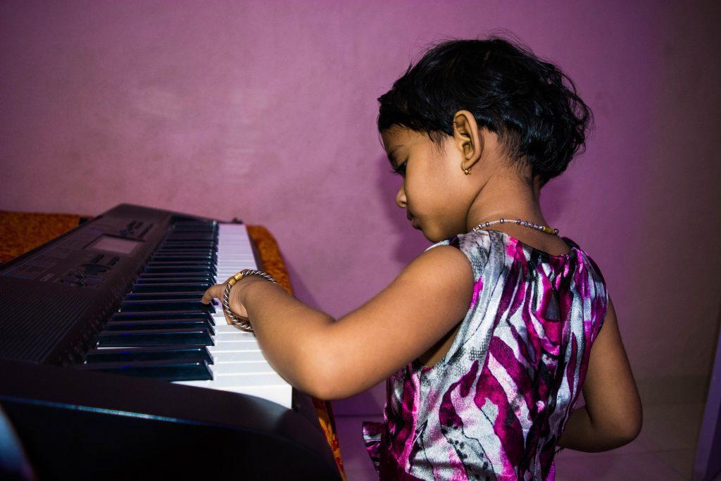 Menina tocando teclado.