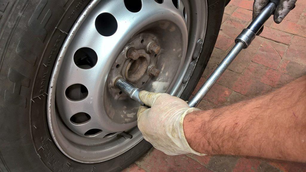 Imagem de uma pessoa trocando o pneu de um carro