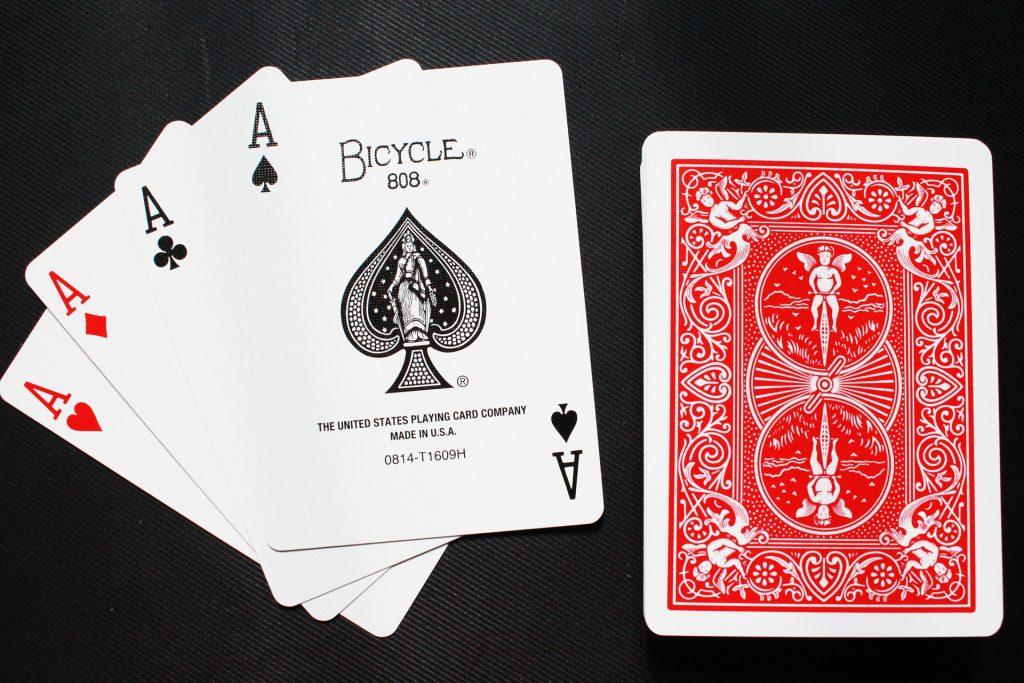 Imagem mostra quatro cartas de um baralho Bicycle, todas ases, dispostas lado à lado e próximos ao restante do maço..