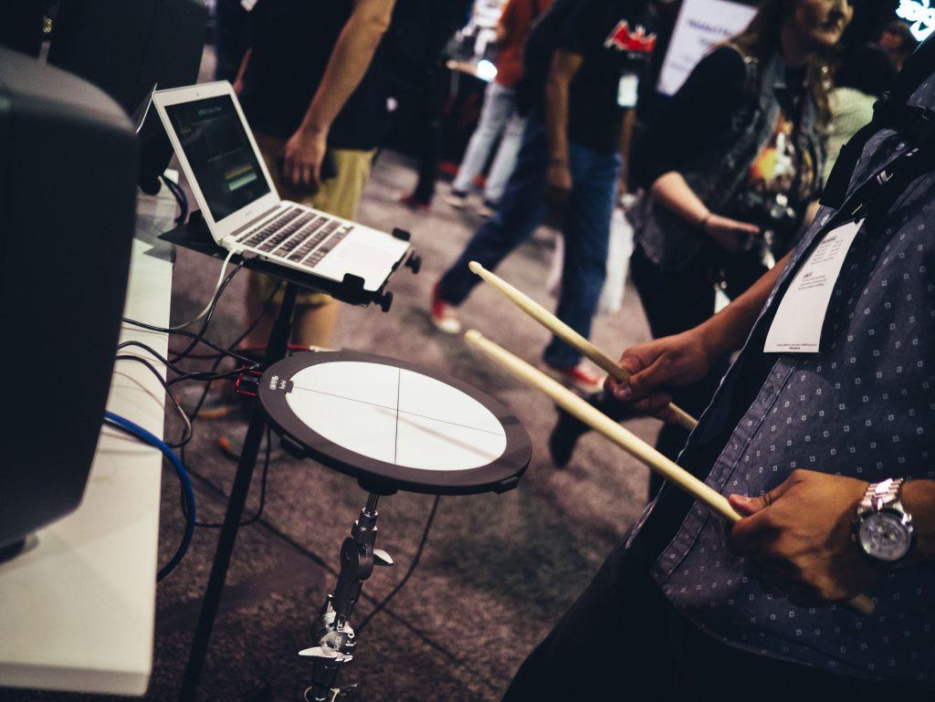 Homem tocando bateria eletrônica conectada ao notebook.