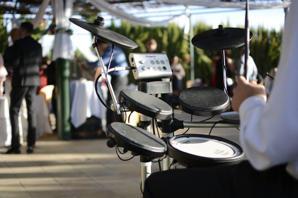 Detalhe de homem tocando bateria eletrônica ao ar livre.