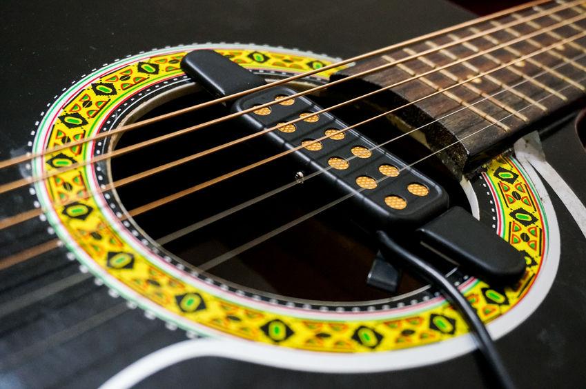 Imagem mostra, em close, um captador de violão já instalado, logo abaixo das cordas.
