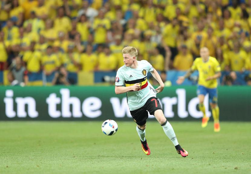 Imagem mostra o meia De Bruyne, da seleção belga, controlando a bola durante um jogo contra a Suécia, que tem um jogador ao fundo do quadro, desfocado.