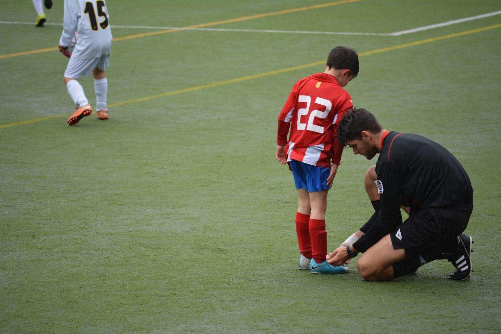 Imagem mostra um árbitro de uma partida de futebol de crianças amarrando as chuteiras Nike de um dos pequenos jogadores.