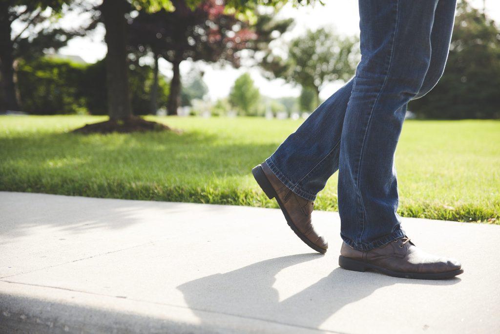 Na foto um homem andando por uma calçada com calça jeans e sapato social.