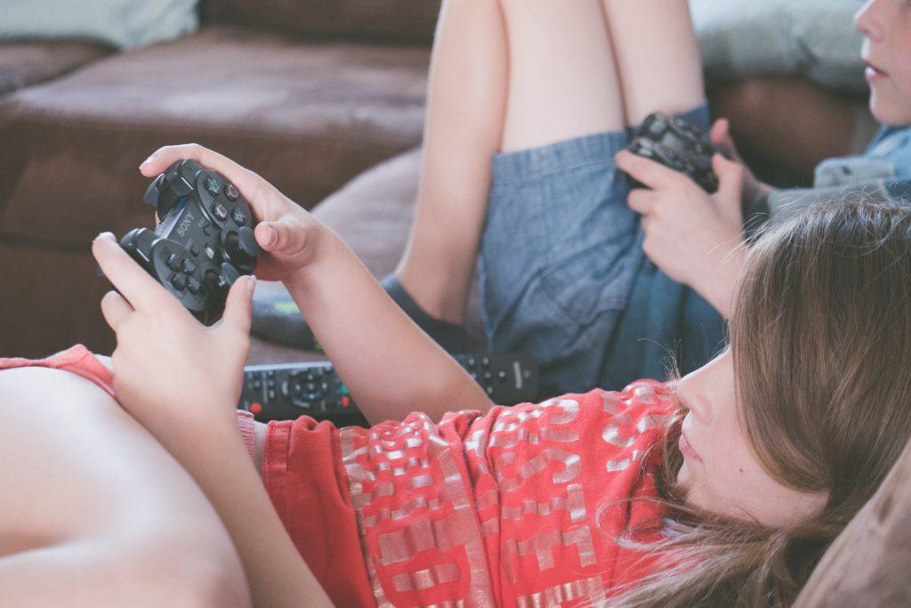 Imagem mostra duas crianças estiradas num sofá, manuseando controles de Playstation.