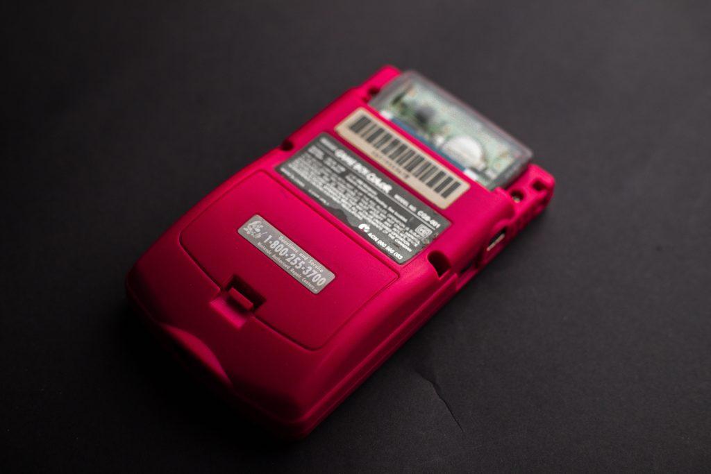 Imagem mostra a parte traseira de um console portátil, com o foco no compartimento de bateria.