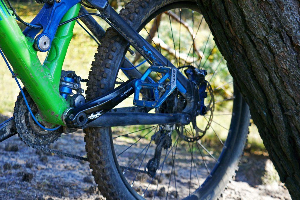 Imagem mostra um close de uma bicicleta de Mountain Bike, focando no pedal esquerdo e nas engrenagens.