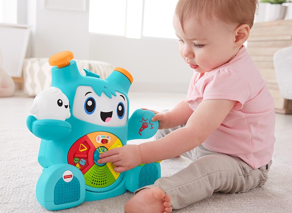 Na foto uma menina sentada no chão brincando com um brinquedo.