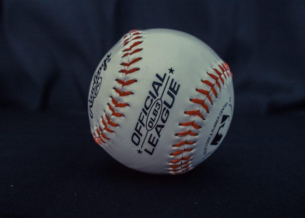 Imagem mostra uma bola de beisebol oficial em plano detalhe, apoiada sobre uma superfície coberta com um tecido, e com a sua textura visível e costuras em destaque.