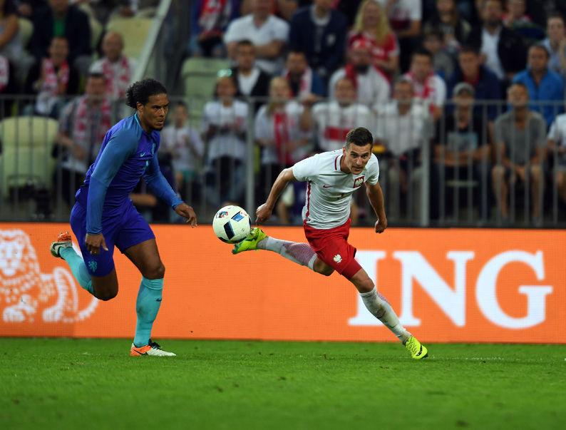 Imagem mostra o zagueiro Virgil Van Dijk, da Holanda, disputando um lance com o atacante Milik, da Polônia. Ambos usam chuteiras Nike.