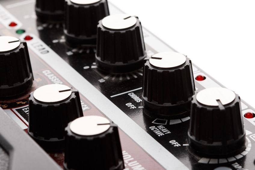 Imagem mostra o close de controladores de volume, tons e frequência.
