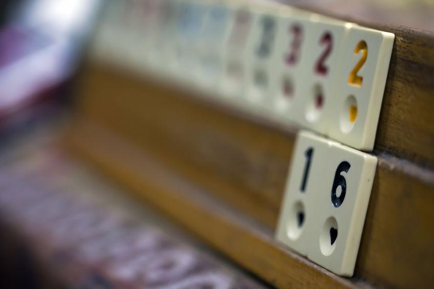 Imagem mostra um suporte de peças de Rummikub com peças apoiadas. O quadro tem foco seletivo nas peças da ponta direita.