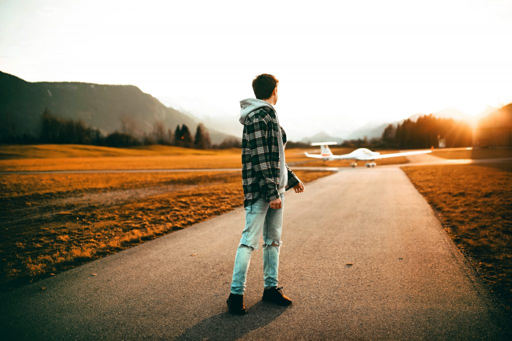 Na foto um homem no meio de uma pista olhando um avião.