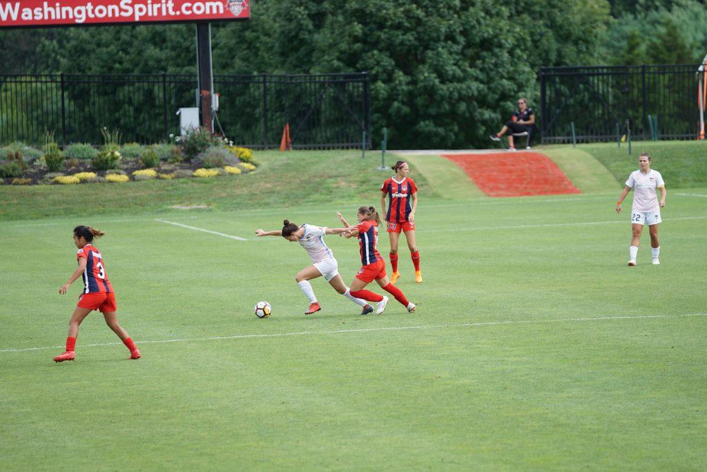 Imagem mostra duas jogadoras próximas à linha do meio campo disputando a bola durante um jogo.
