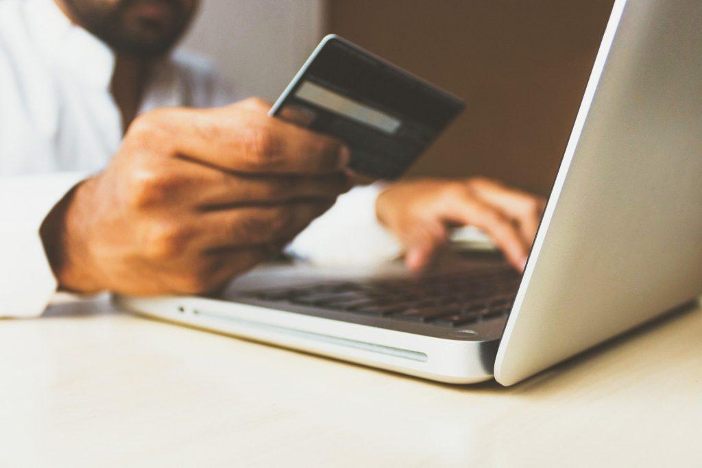 Homem segurando cartão de crédito em uma mão e digitando no notebook em outra.