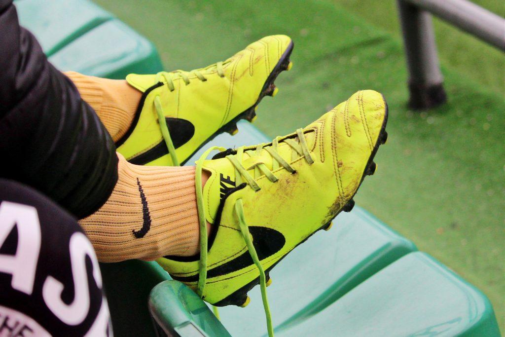 Imagem mostra dois pés apoiados num banco e com chuteiras Nike apenas apoiadas nas suas pontas.