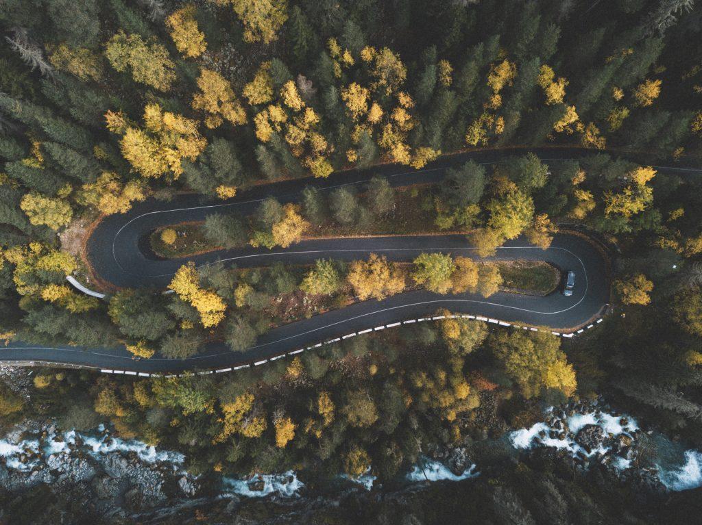 Imagem mostra uma tomada aérea de um trecho de uma estrada, com curvas sinuosas e muitas árvores na encosta.