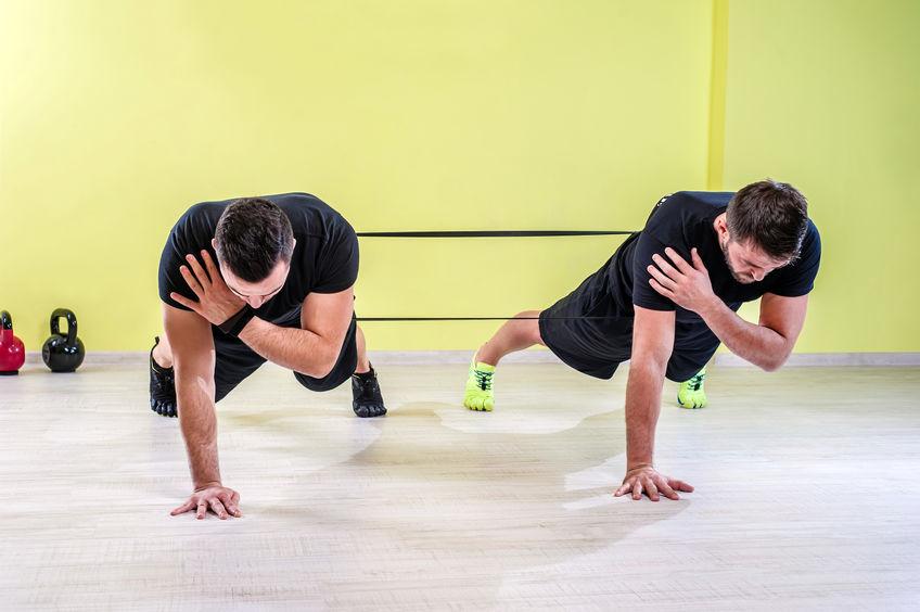 Dois homens treinando juntos com mini band preta.