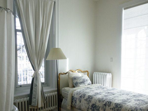 Foto de um quarto de solteiro com paleta de cores branca e azul clara. Há uma cama, um abajur, e uma cortina com abraçadeira em frente a uma janela.