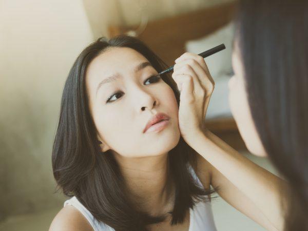 Moça aplica delineador em caneta nos olhos em frente ao espelho