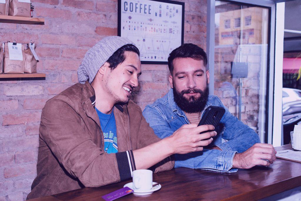 Dois homens tomando café, enquanto um mostra seu smartphone, eles riem. Há um cartão Nubank sobre a mesa apoiado no pires.