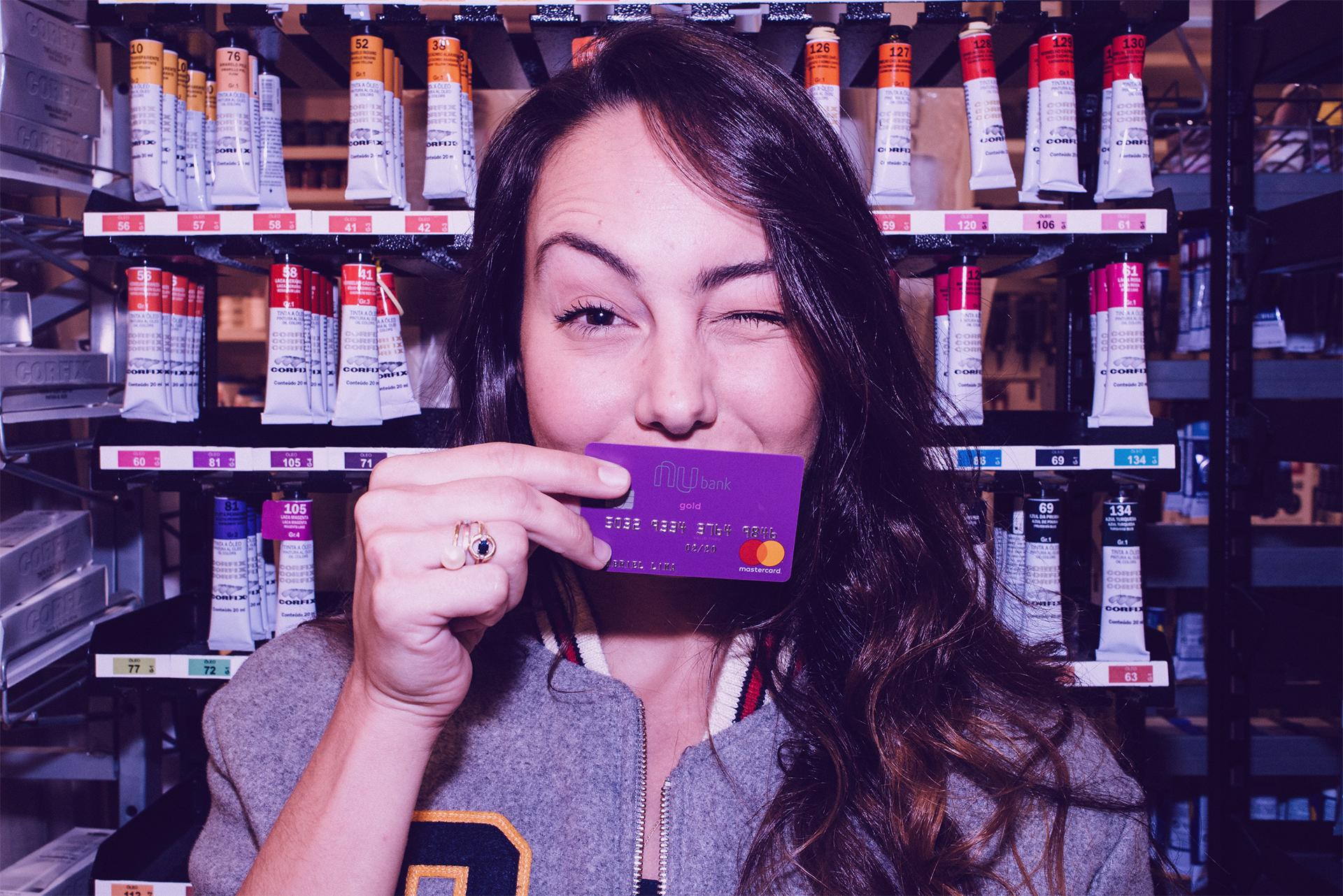 Mulher piscando com cartão Nubank na frente do rosto