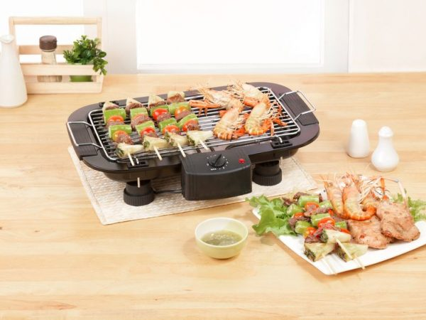 Imagem de uma panela elétrica sobre bancada com legumes dentro e temperos e outros utensílios ao redor.