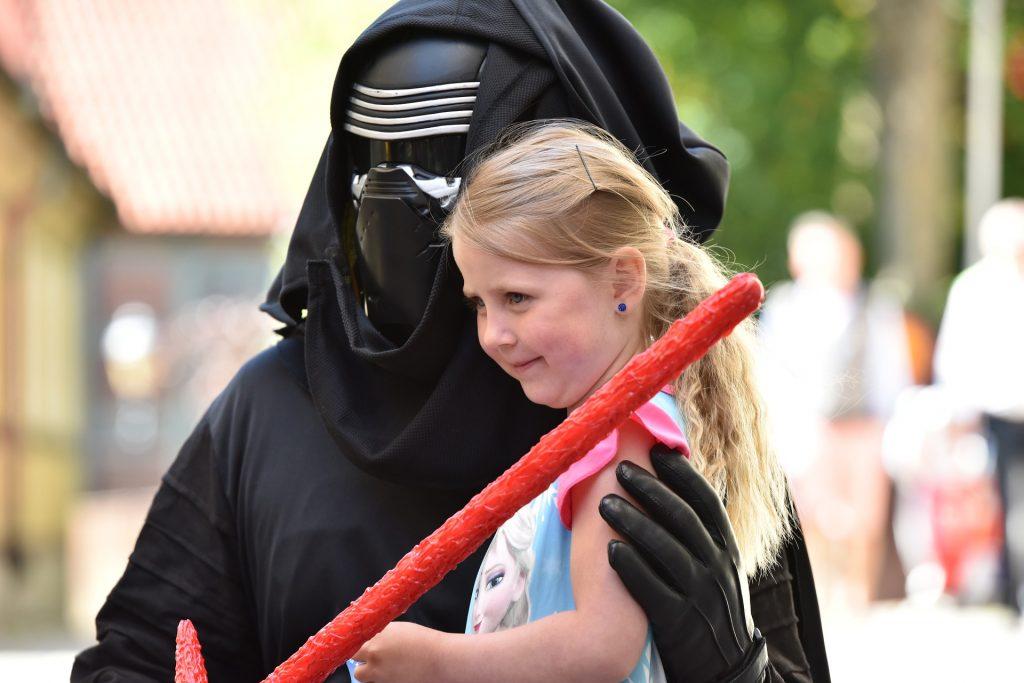 Imagem de ator vestido de Kylo Ren ao lado de criança, segurando um sabre de luz vermelho
