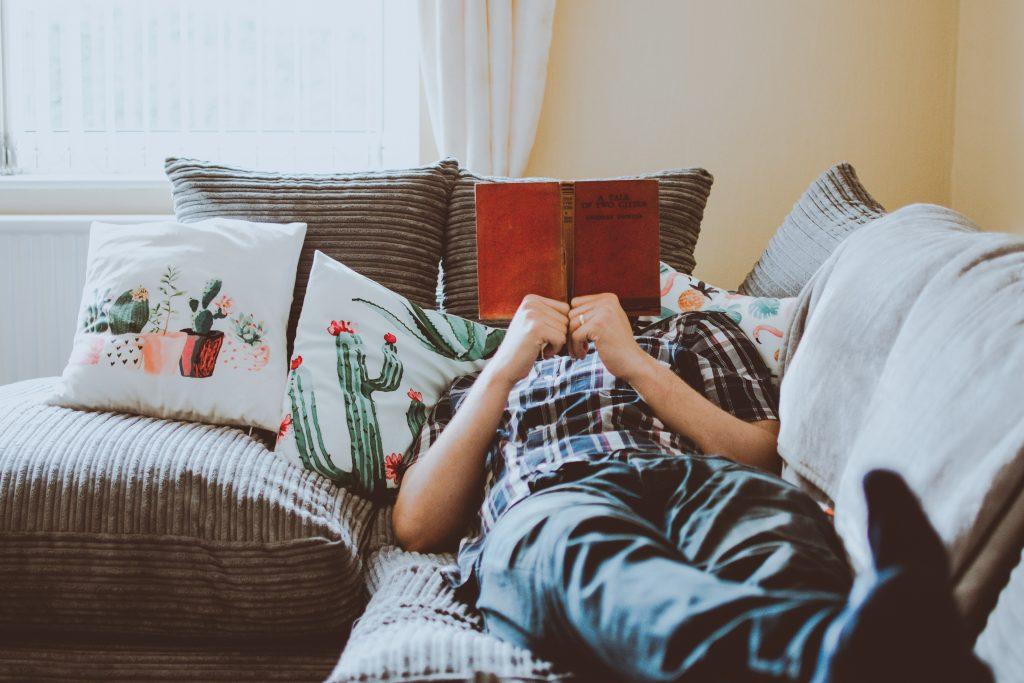 Foto de um homem deitado em um sofá cinza, em meio a almofadas cinzas e estampadas de cactus, lendo um livro vermelho, que tampa o seu rosto.