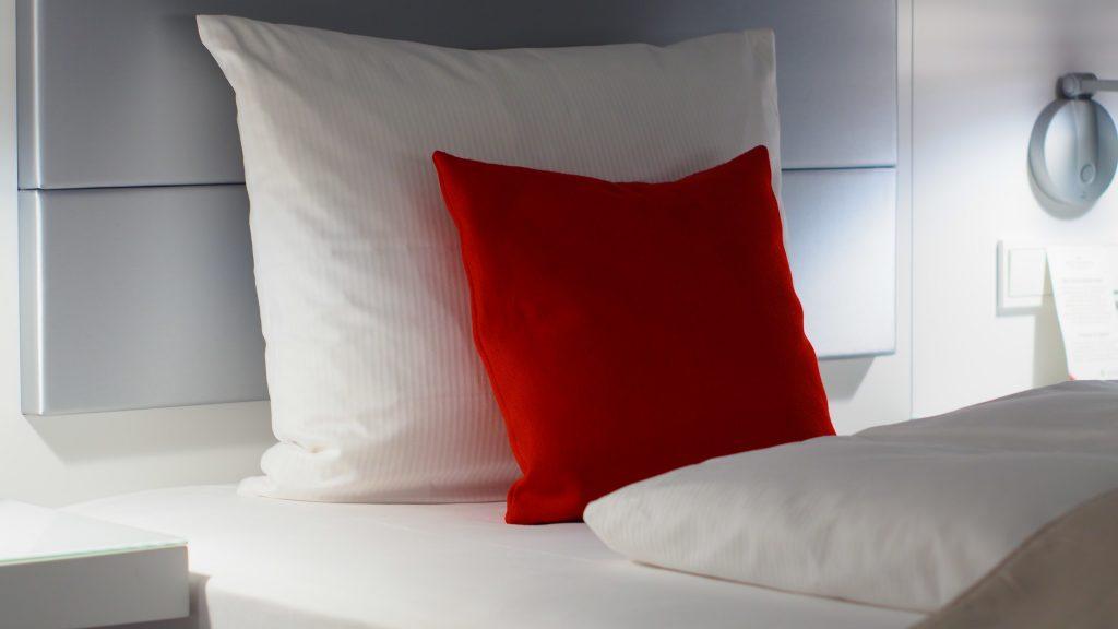 Foto de dois travesseiros branco e uma almofada vermelha, os três em cima de uma cama de casal com design moderno.