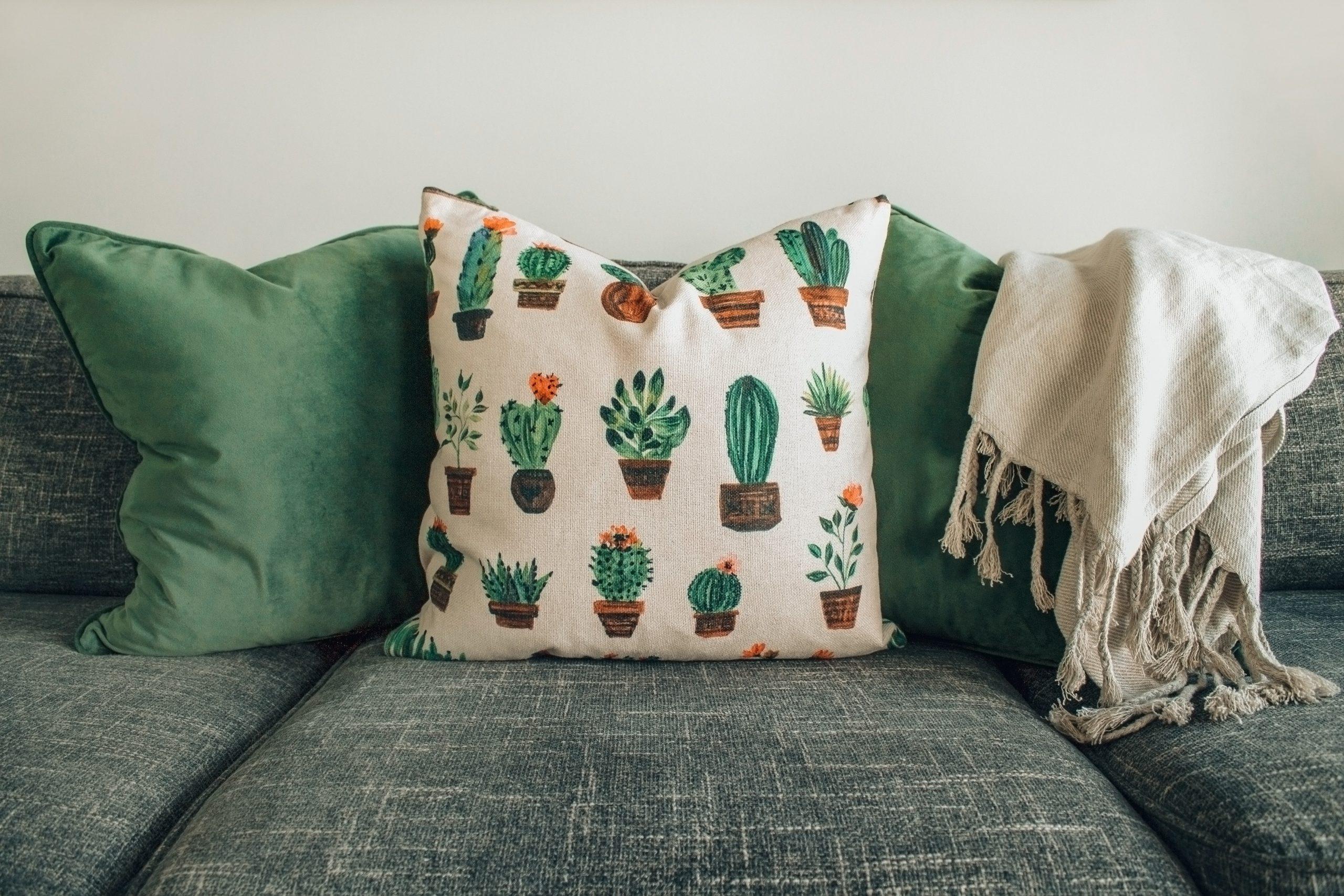 Foto de três almofadas, sendo que duas são verdes e uma é branca com estampa de cactos. Junto delas, uma coberta bege levinha.