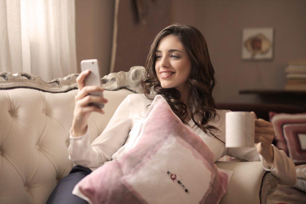 Foto de uma mulher sorridente sentada no sofá com uma almofada no colo. Com um das mãos ela segura o celular e com a outra um xícara branca.
