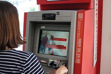 Mulher fazendo saque em caixa eletrônico da rede Banco24Horas.