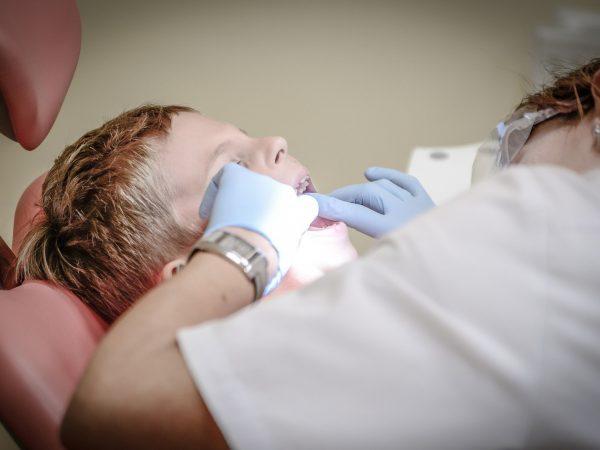 Dentista tratando de dente de criança no consultório.