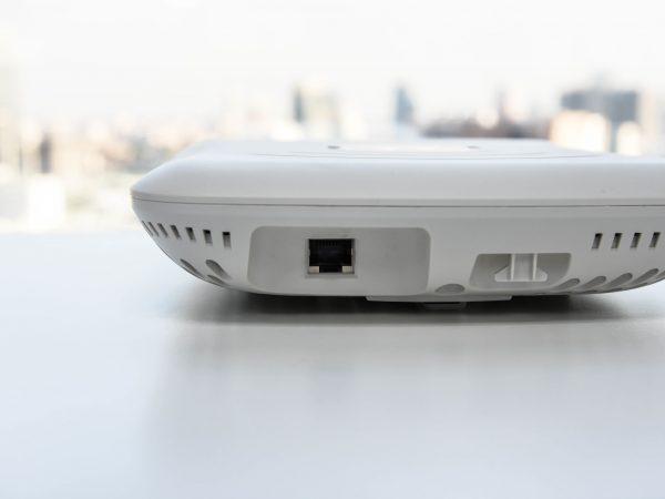 Imagem mostra um dispositivo access point sobre uma mesa branca.
