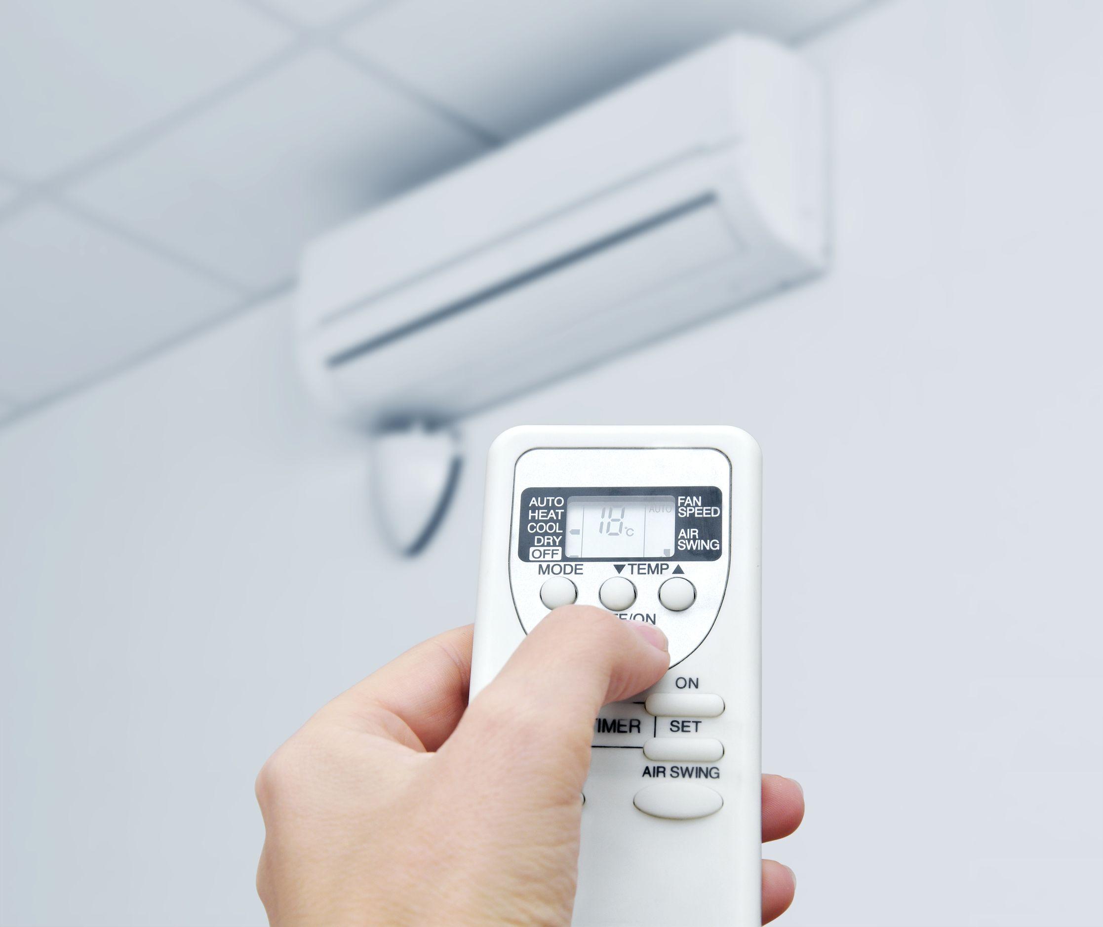 Imagem de uma mão segurando um controle mirando em direção a um ar-condicionado colocando suplementos e frutas no liquidificador