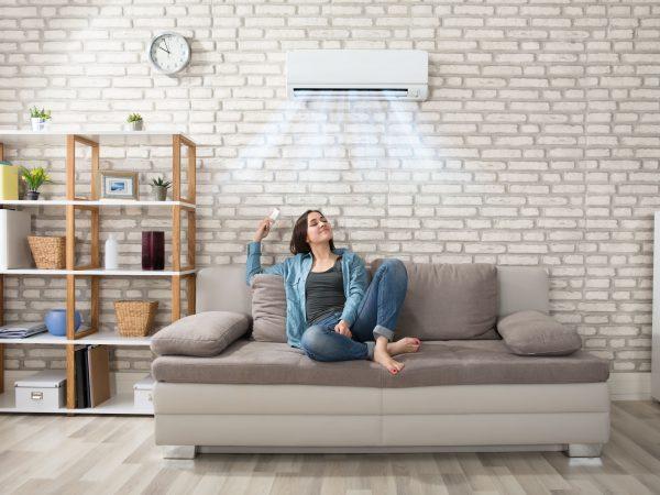 Na foto uma mulher sentada em um sofá embaixo de um ar condicionado.