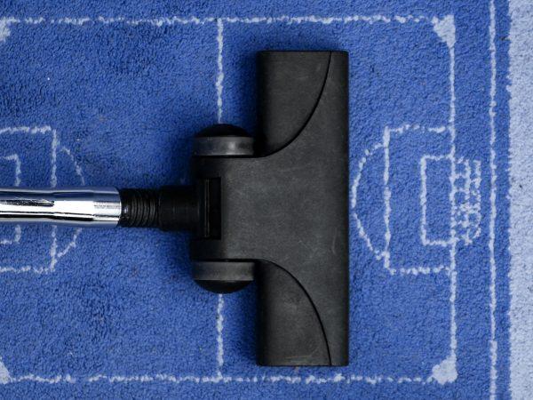 Aspirador de pó limpando tapete com estampa de campo de futebol