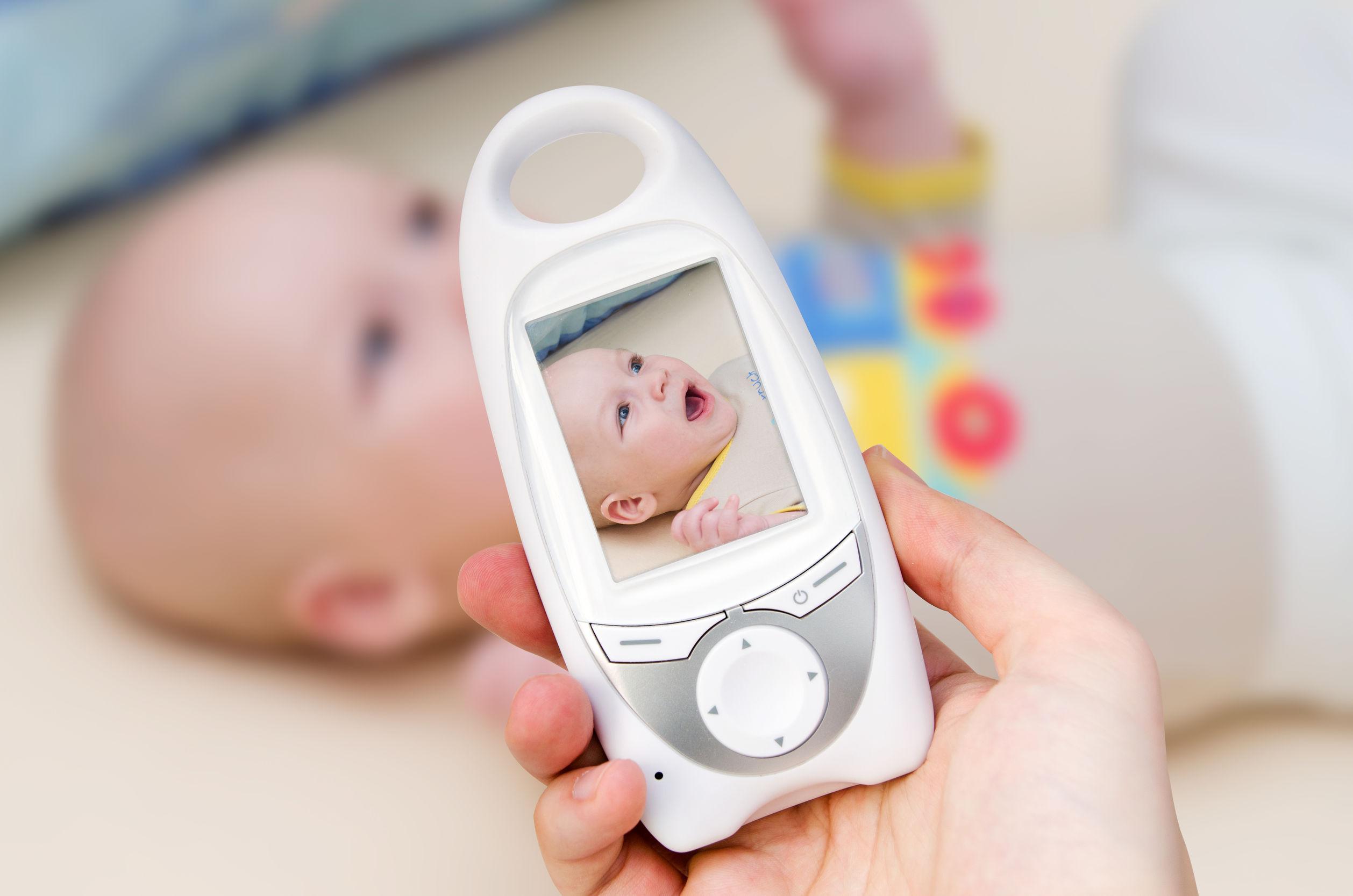 Mão segurando monitor de babá eletrônica com bebê em visor e em segundo plano.