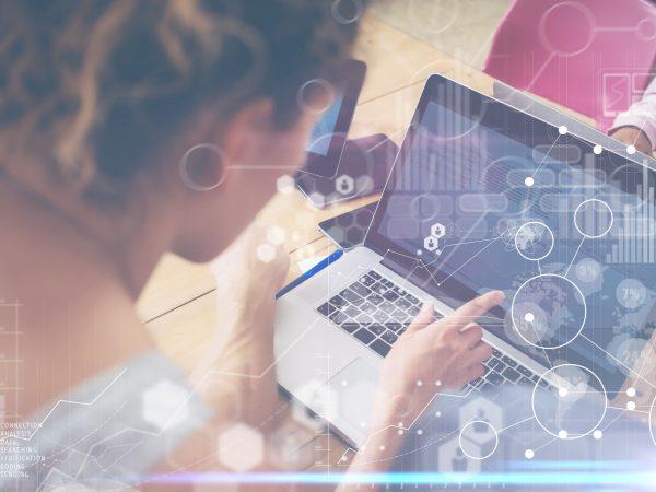 Mulher usando notebook com imagens digitais sobre a foto