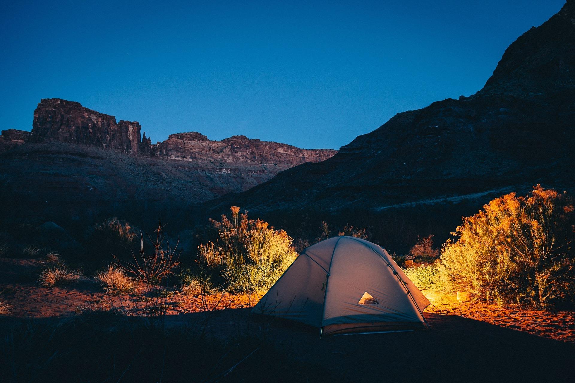 Imagem mostra uma barraca montada num ambiente árido, ao fim da tarde. Uma luz de lanterna emana da barraca.