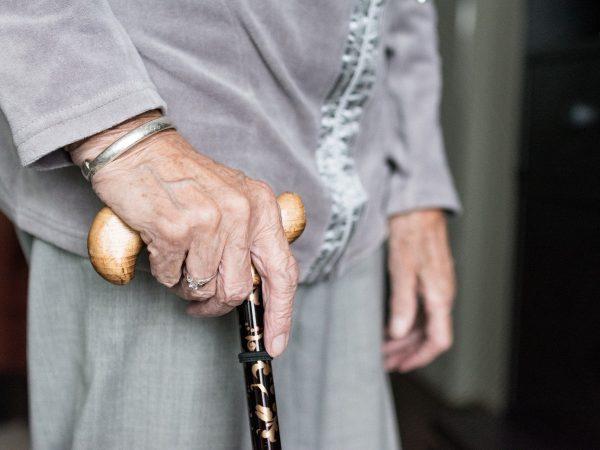 Imagem mostra uma pessoa em pé segurando uma bengala