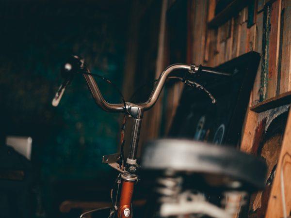 Imagem mostra um close de uma bicicleta com o foco seletivo. O selim está desfocado em primeiro plano, e o guidão, focado, está em segundo plano.