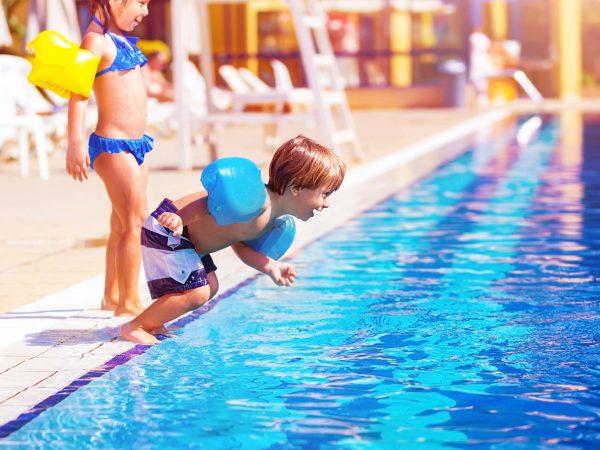 Na foto duas crianças usando boias de braço na beira de uma piscina.