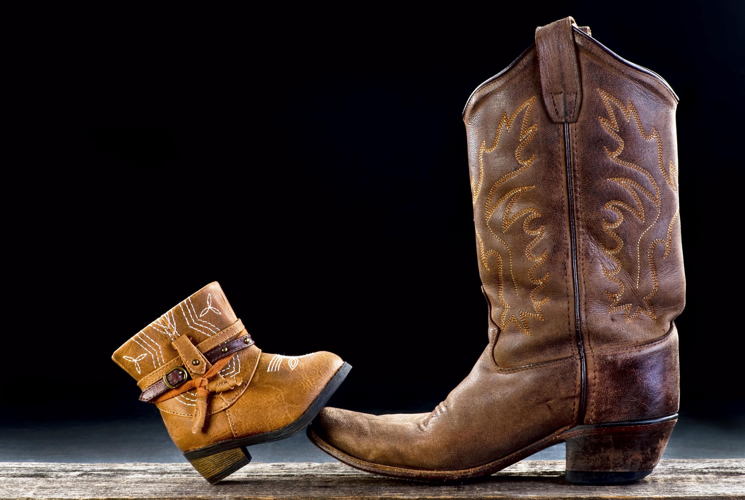 Na foto duas botas texanas sendo uma feminina adulto e uma infantil.